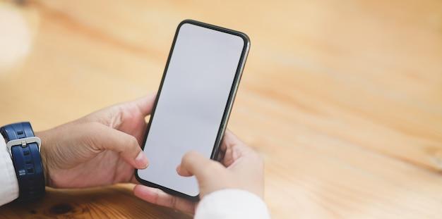Nahaufnahme der hände der frau, die smartphone des leeren bildschirms halten Premium Fotos