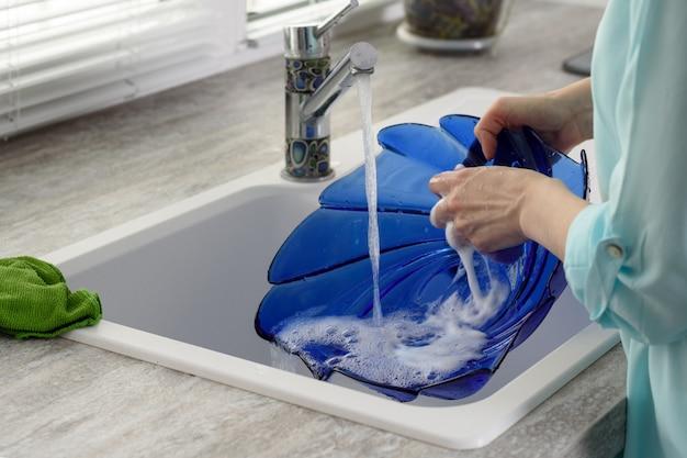 Nahaufnahme der hände der frauen für das waschen des geschirrs, das konzept von hausarbeiten Premium Fotos