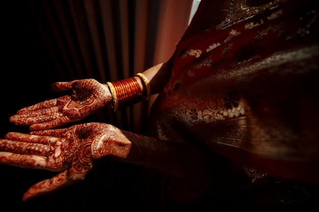 Nahaufnahme der hände der hindischen braut bedeckt mit hennastrauchtätowierungen Kostenlose Fotos