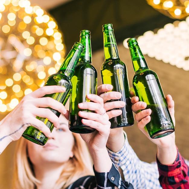Nahaufnahme der hände des freundes, welche die bierflaschen klirren Kostenlose Fotos