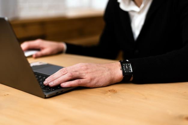 Nahaufnahme der hände eines mannes, die auf einer laptop-tastatur tippen. beschnittenes bild eines jungen mannes, der an seinem laptop in einem café arbeitet Premium Fotos