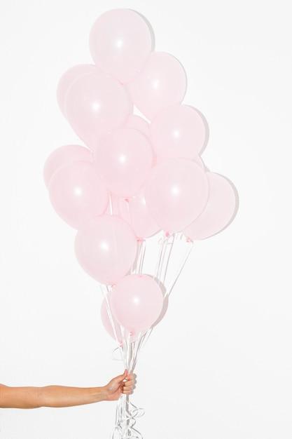 Nahaufnahme der hand bündel rosa ballone gegen weißen hintergrund halten Kostenlose Fotos