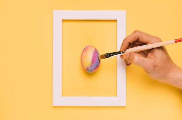 Nahaufnahme der hand das osterei mit bürste innerhalb des rahmens auf gelbem hintergrund malend Kostenlose Fotos