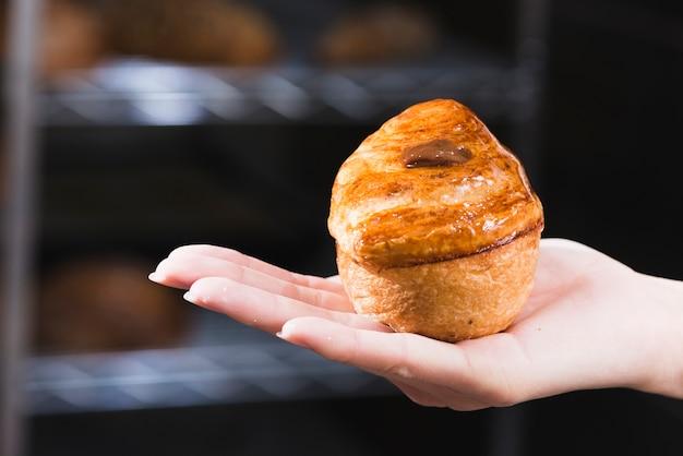 Nahaufnahme der hand der frau frisch gebackenen süßen blätterteig halten Kostenlose Fotos