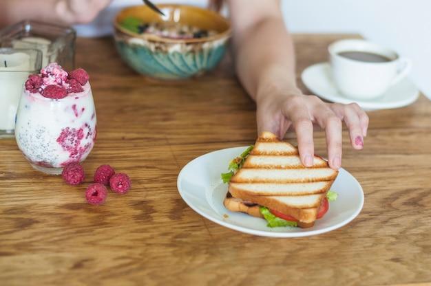Nahaufnahme der hand der frau sandwich von der keramischen platte auf holztisch nehmend Kostenlose Fotos