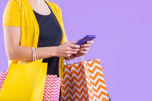 Nahaufnahme der hand der frau unter verwendung der weißen tragenden einkaufstasche des mobiltelefons Kostenlose Fotos