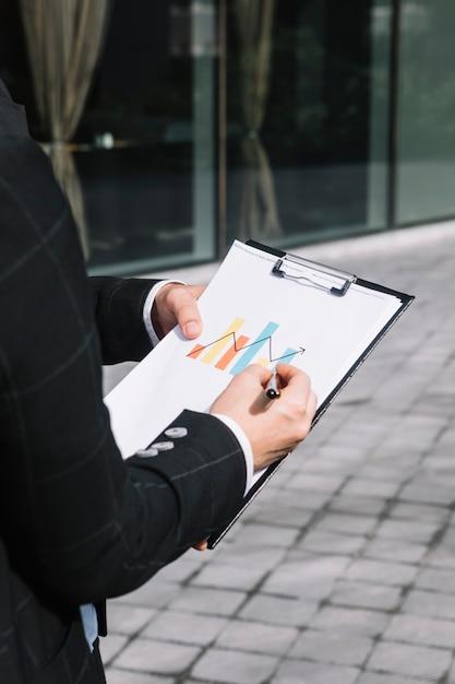 Nahaufnahme der hand der geschäftsperson, die zunehmenden pfeil auf diagramm über der zwischenablage zeichnet Kostenlose Fotos