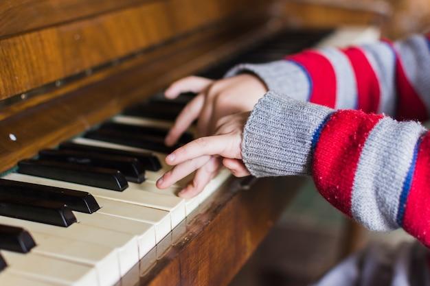 Nahaufnahme der hand der jungen, die klaviertasten spielt Kostenlose Fotos