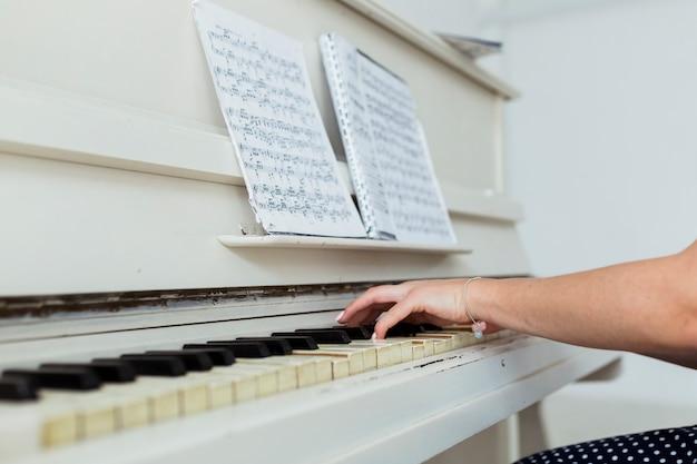 Nahaufnahme der hand der jungen frau, die das klavier spielt Kostenlose Fotos