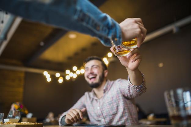 Nahaufnahme der hand der person, die getränke mit seinem freund röstet Kostenlose Fotos