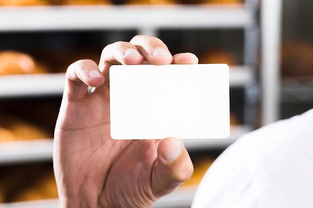 Nahaufnahme der hand des männlichen bäckers, die leere weiße visitenkarte hält Kostenlose Fotos
