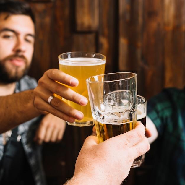 Nahaufnahme der hand des männlichen freundes, die gläser alkoholische getränke röstet Kostenlose Fotos