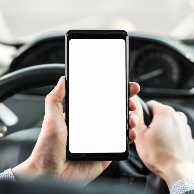 Nahaufnahme der hand des mannes das auto fahren, das leeren weißen bildschirmhandy zeigt Kostenlose Fotos