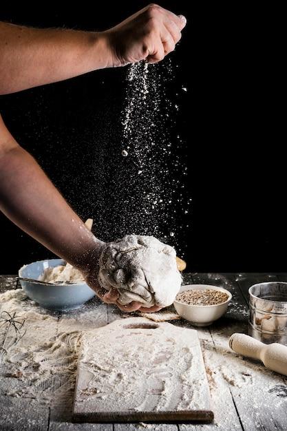 Nahaufnahme der hand des mannes das mehl auf dem teig spritzend Kostenlose Fotos