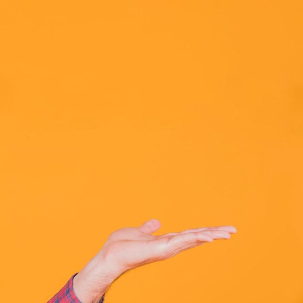 Nahaufnahme der hand des mannes, die etwas gegen einen orange hintergrund darstellt Kostenlose Fotos
