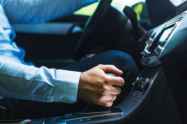 Nahaufnahme der hand des mannes, die gang im auto schiebt Kostenlose Fotos