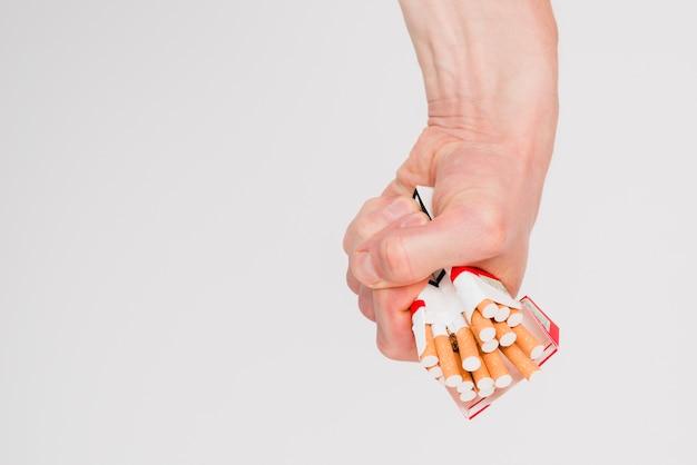Nahaufnahme der hand des mannes eine schachtel zigaretten zerquetschend Premium Fotos