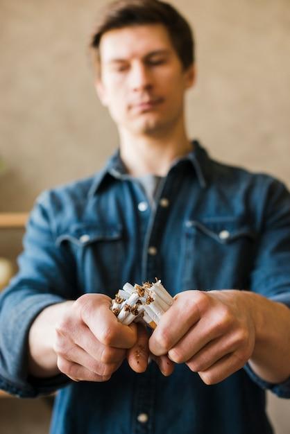 Nahaufnahme der hand des mannes gebrochenes bündel zigaretten Kostenlose Fotos
