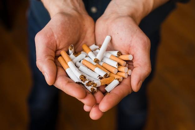Nahaufnahme der hand des mannes mit bündel des brechens der zigarette Kostenlose Fotos