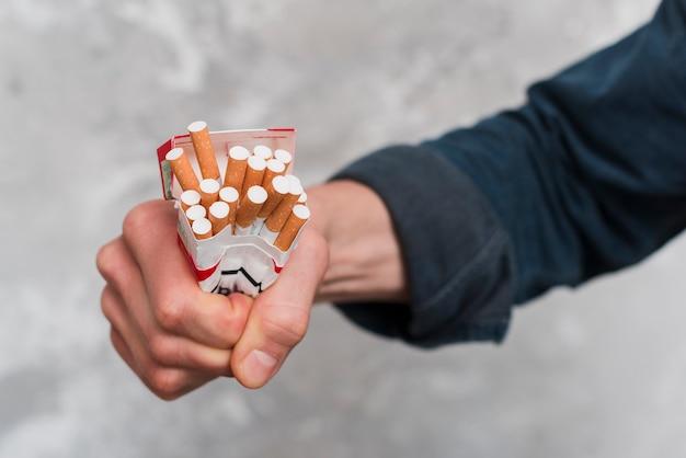 Nahaufnahme der hand des mannes zigarettenkasten zerquetschend Kostenlose Fotos