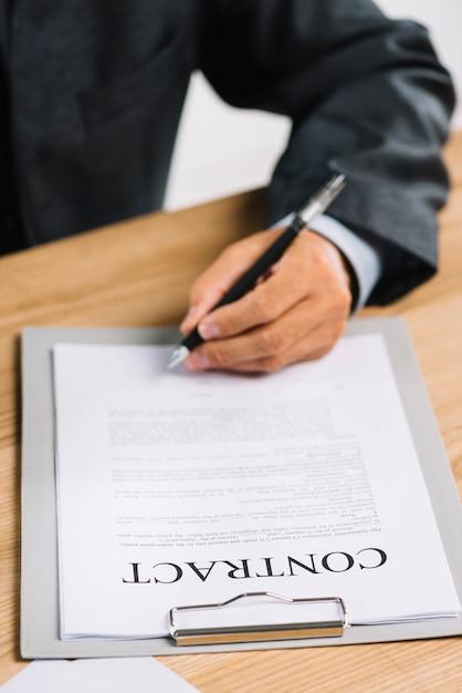 Nahaufnahme der hand des rechtsanwalts ein offizielles dokument unterzeichnend Kostenlose Fotos