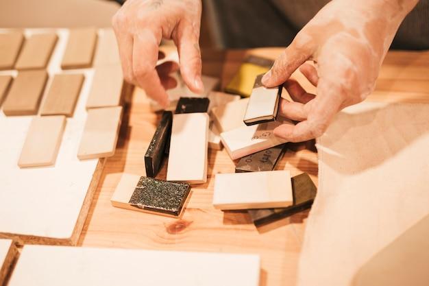 Nahaufnahme der hand des weiblichen töpfers arbeitend mit keramikfliesen auf tabelle Kostenlose Fotos