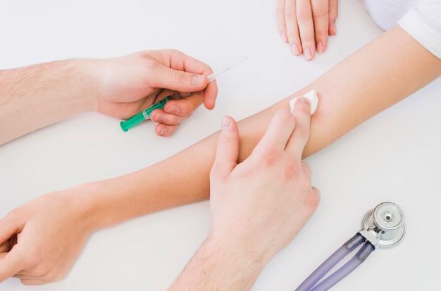 Nahaufnahme der hand doktors, die baumwolle über der hand des patienten hält, nachdem die spritze auf weißem schreibtisch gegeben worden ist Premium Fotos