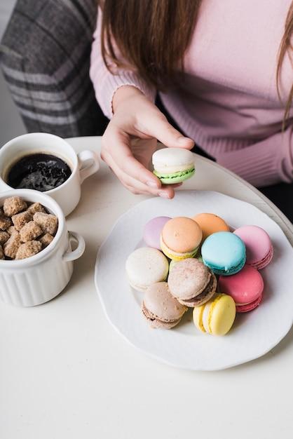 Nahaufnahme der hand einer frau, die makrone mit würfel des kaffees und des braunen zuckers in der schale auf tabelle hält Kostenlose Fotos