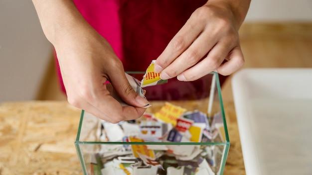 Nahaufnahme der hand einer frau, die papierstücke macht Kostenlose Fotos