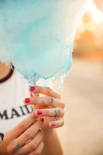 Nahaufnahme der hand einer frau mit blauer zuckerwatte Kostenlose Fotos
