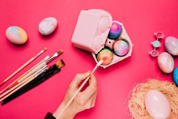 Nahaufnahme der hand einer person, die das ei mit pinsel im karton auf rosa hintergrund malt Kostenlose Fotos