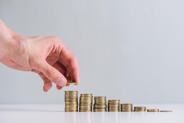 Nahaufnahme der hand einer person, die goldene münzen stapelt Kostenlose Fotos