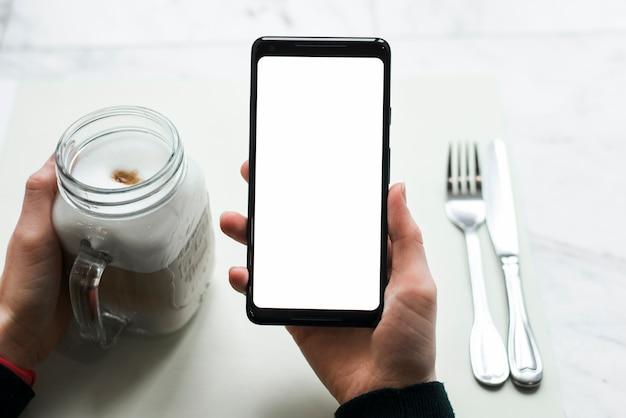 Nahaufnahme der hand einer person, die intelligentes telefon mit smoothieglas hält Kostenlose Fotos