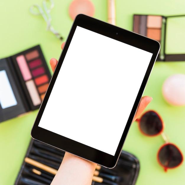 Nahaufnahme der hand einer person, die leeren digitalen tablettenschirm über kosmetik zeigt Kostenlose Fotos