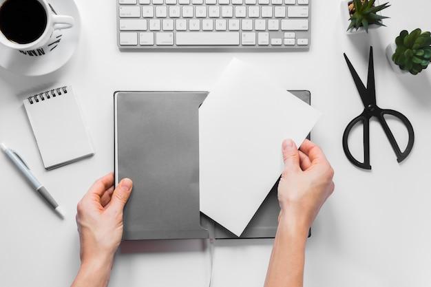 Nahaufnahme der hand einer person, die leeres weißbuch in die graue abdeckung auf arbeitsplatzschreibtisch einfügt Kostenlose Fotos