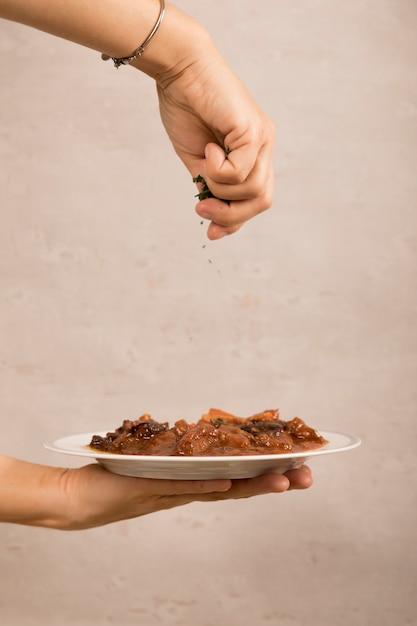 Nahaufnahme der hand einer person, die mexikanischen rindfleischgericht schmückt Kostenlose Fotos