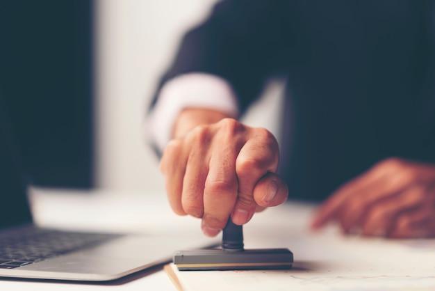 Nahaufnahme der hand einer person, die mit anerkanntem stempel auf dokument am schreibtisch stempelt Premium Fotos