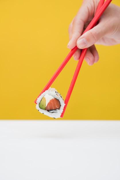 Nahaufnahme der hand einer person, die sushirolle mit roten essstäbchen gegen gelben hintergrund hält Kostenlose Fotos
