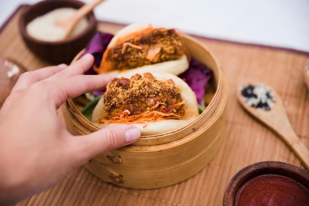 Nahaufnahme der hand einer person, die taiwans traditionellen lebensmittel gua bao im dampfer hält Kostenlose Fotos