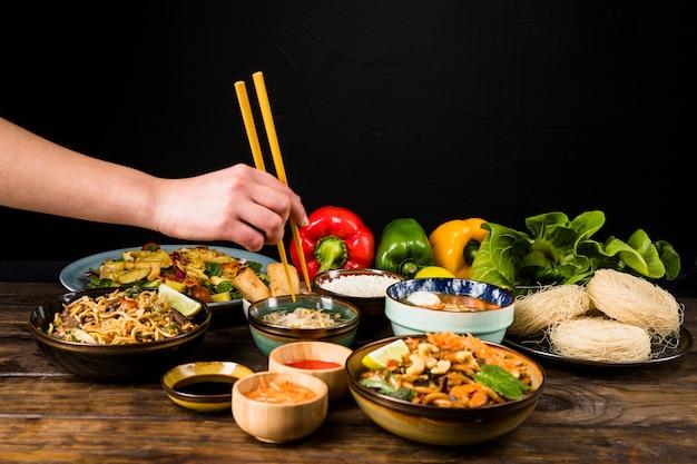 Nahaufnahme der hand einer person, die thailändisches lebensmittel mit essstäbchen auf tabelle gegen schwarzen hintergrund isst Kostenlose Fotos