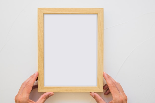 Nahaufnahme der hand einer person, die weißen holzrahmen auf wand hält Kostenlose Fotos