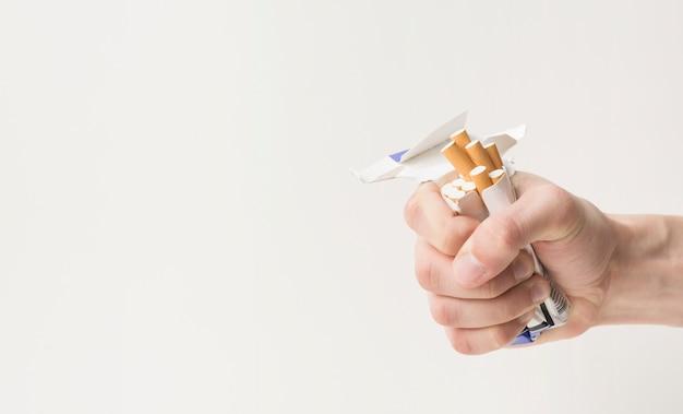 Nahaufnahme der hand einer person, die zigaretten und kasten zerknittert Kostenlose Fotos
