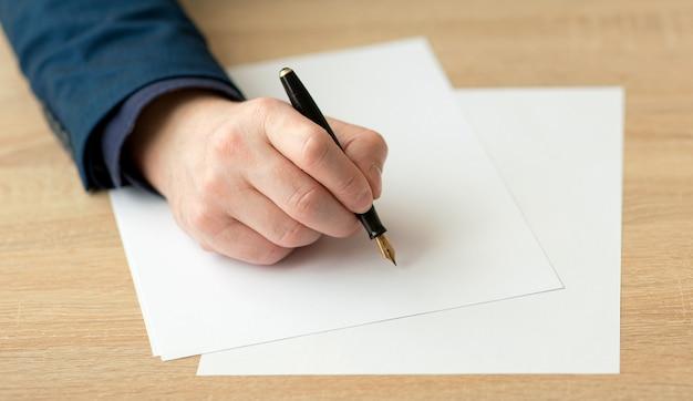 Nahaufnahme der hand eines geschäftsmannes in einem anzug, der einen brief schreibt oder ein dokument auf einem stück weißem papier mit einem füllfederhalter mit feder unterschreibt Premium Fotos