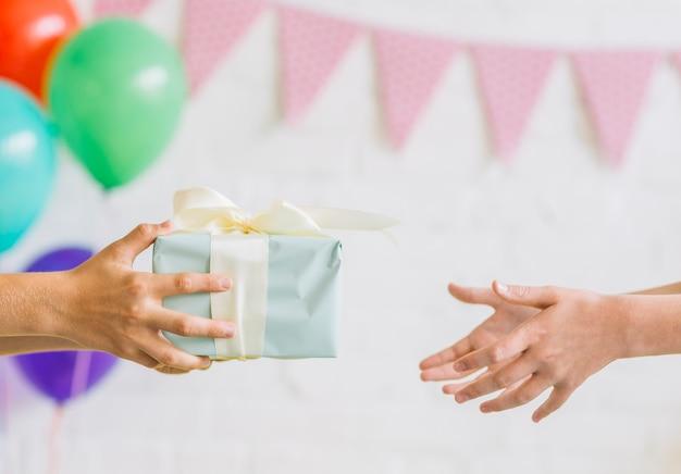 Nahaufnahme der hand eines jungen, die seinem freund geburtstagsgeschenk gibt Kostenlose Fotos