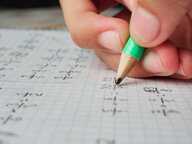 Nahaufnahme der hand eines jungen mädchens, das mathe-hausaufgaben macht, keine gesichter gezeigt, nur hand und bleistift, bildungskonzept, nahaufnahme Premium Fotos