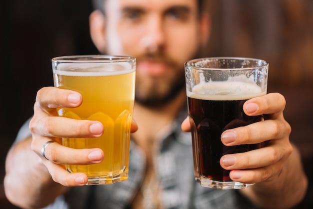 Nahaufnahme der hand eines mannes, die gläser bier und rum hält Kostenlose Fotos