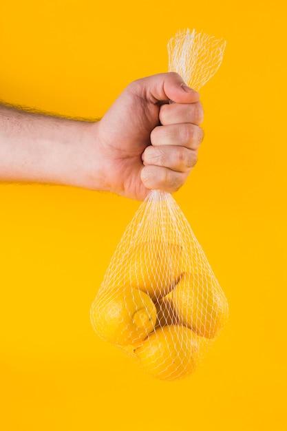 Nahaufnahme der hand eines mannes, welche die reifen zitronen im netz gegen gelben hintergrund hält Kostenlose Fotos
