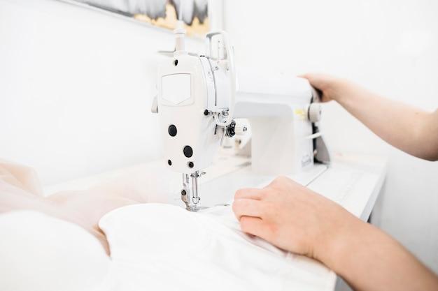 Nahaufnahme der hand eines weiblichen designers, die an nähmaschine arbeitet Kostenlose Fotos