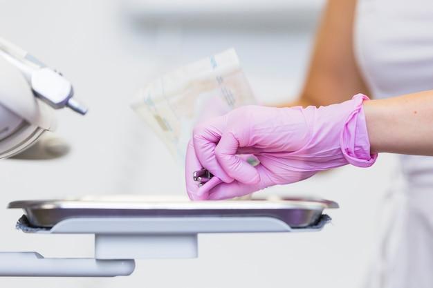 Nahaufnahme der hand eines zahnarztes, die zahnmedizinische werkzeuge anhält Kostenlose Fotos