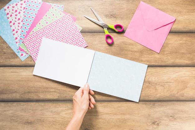 Nahaufnahme der hand leeres kartenpapier gegen hölzernen hintergrund halten Kostenlose Fotos